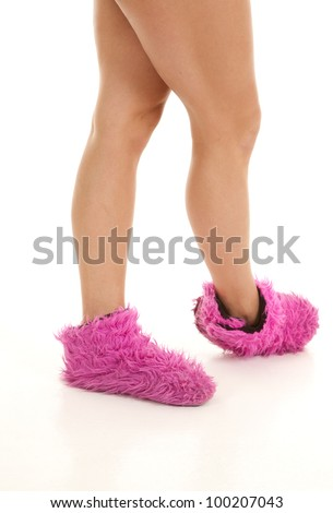 A woman in her fuzzy pink slippers standing.