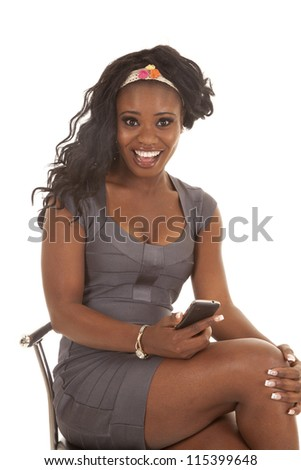 a woman in her gray dress with a shocked expression on her face holding on to her cell phone - stock photo