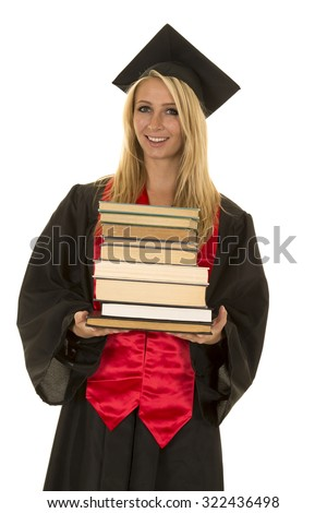 a woman in her her cap and gown holding a stack of books with a smile.
