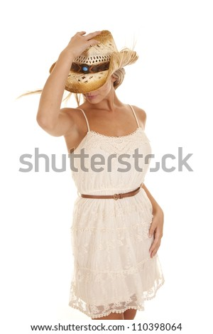 A woman in her lace dress looking down holding on to her hat with the wind blowing her hair. - stock photo