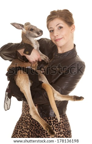 a woman in her leather jacket with a small smile on her face holding on to her pet kangaroo. - stock photo