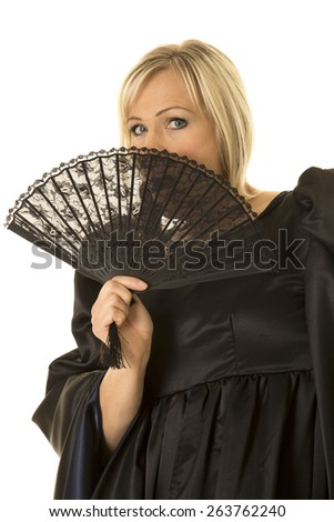 A woman in her medieval dress, hiding behind a black fan. - stock photo