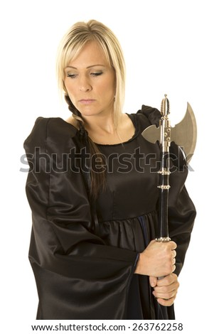 A woman in her medieval dress holding on to a hatchet. - stock photo