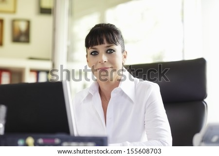 A woman in her mid thirties sits at a desk in front of a laptop screen.