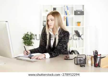 A woman in her mid thirties sitting in front of her computer,working in her office - stock photo
