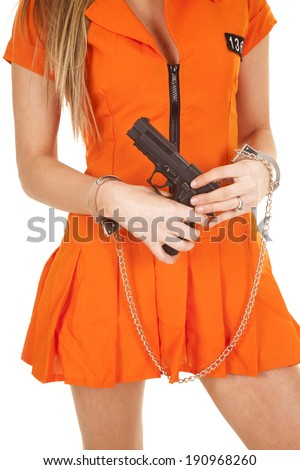 a woman in her orange jump suit with her gun, and hand cuffs on. - stock photo