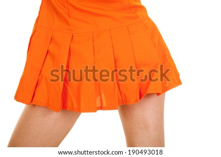 A woman in her orange skirt, with her back to the camera. - stock photo