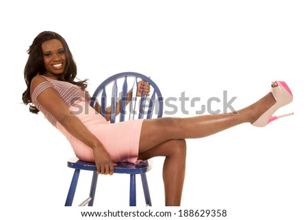 A woman in her pink dress and high heels, leaning back on a blue chair with a smile.