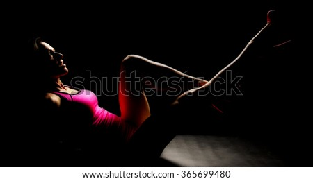 A woman in her pink shoes and clothing in the shadows. - stock photo