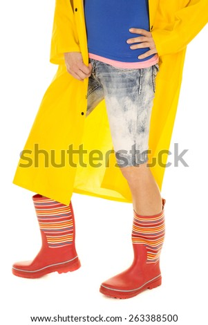 A woman in her rain boots and coat standing. - stock photo