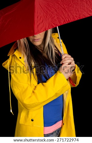 a woman in her rain coat with a red umbrella hiding her face. - stock photo