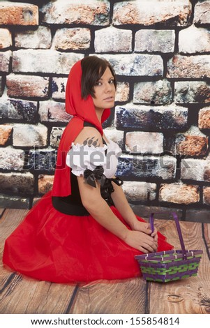 A woman in her red hood and dress with a wolf paw print on her shoulder. - stock photo