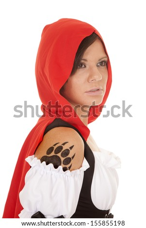 A woman in her red hood looking away with her paw print tattoo on her shoulder. - stock photo