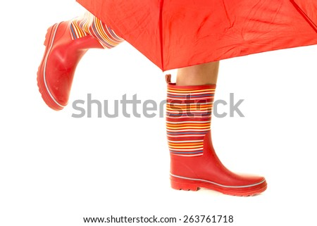 A woman in her red rain boots walking, with her umbrella showing. - stock photo