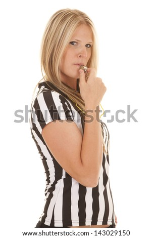 A woman in her referee shirt blowing on her whistle with a serious expression - stock photo