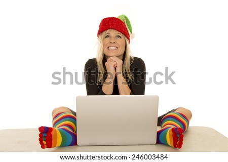 A woman in her Santa hat with her finger up to her mouth looking at the computer with her feet up with multicolored socks. - stock photo