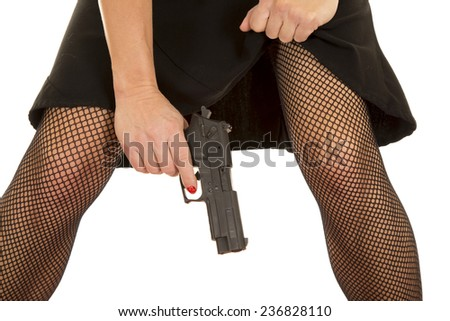 a woman in her skirt and fishnets holding on to a pistol. - stock photo