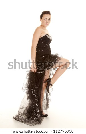 A woman in her sparkling black formal with her foot up by her knee with a serious expression on her face. - stock photo