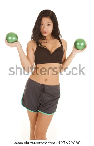 A woman in her sports bra and shorts working out with weighted green balls.