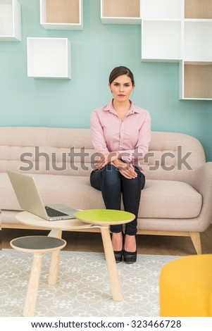 A woman in her thirties is sitting on a sofa in a stylish vintage waiting room with pastels colors. She is looking at camera with her arms crossed, wearing a pink shirt and slim jeans, her laptop next - stock photo