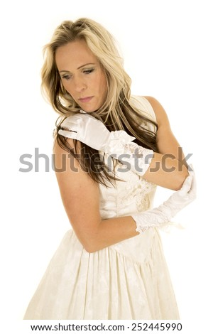 A woman in her vintage wedding dress hugging herself - stock photo