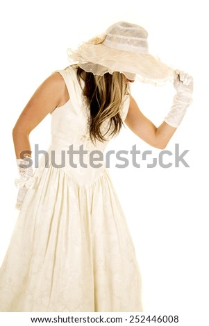 A woman in her vintage wedding dress walking away holding on to her hat. - stock photo