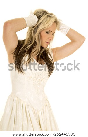 A woman in her vintage white dress, with her hands up in her hair.