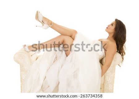 A woman in her wedding dress looking up. - stock photo