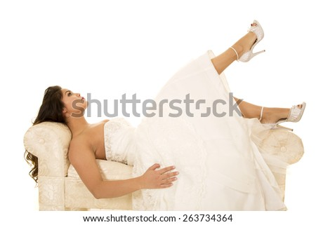 A woman in her wedding dress with her legs kicked up. - stock photo