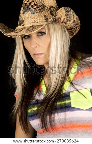 a woman in her western hat looking with a serious expression on her face. - stock photo