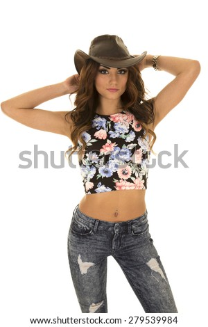 A woman in her western hat, with her hands up by her head. - stock photo