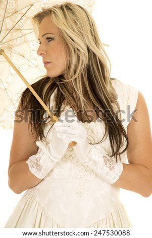 A woman in her white dress and gloves and umbrella looking to the side. - stock photo