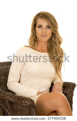 A woman in her white dress sitting with a small smile. - stock photo