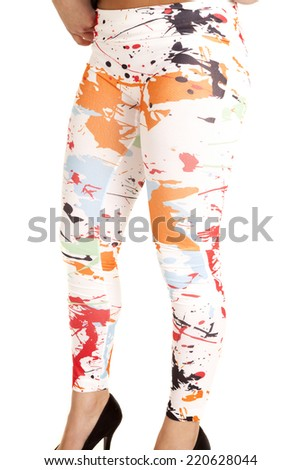 A woman in her white paint splat leggings standing. - stock photo