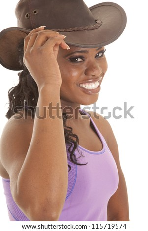 a woman in her workout top with a smile on her face holding on to the brim of her hat - stock photo