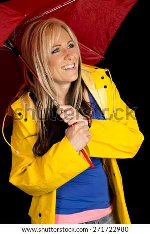 a woman in her yellow rain coat with a big smile on her face, hiding under her umbrella. - stock photo