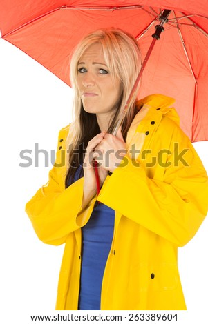 a woman in her yellow rain coat with a sad expression on her face. - stock photo