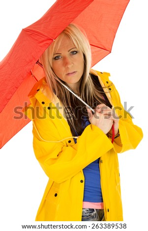 A woman in her yellow rain coat with a serious expression, hiding under her red umbrella. - stock photo