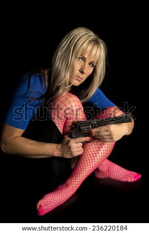 A woman in pink fishnet stockings holding a gun. - stock photo