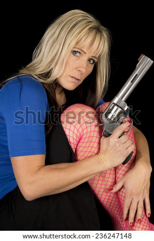 A woman in pink fishnet stockings sitting holding a gun. - stock photo