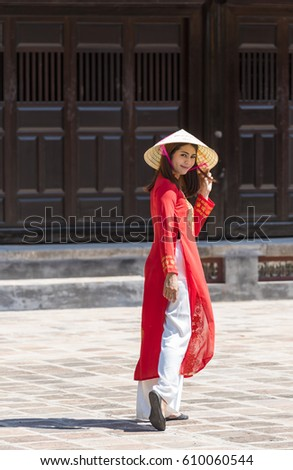 a woman in red ao dai Vietnamese's traditional costumes walking in the ancient city