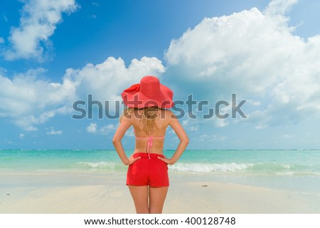 A woman in red-hat on a background of the tropical sea - stock photo