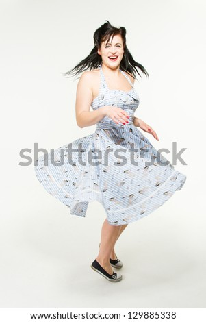 A woman in 1950s retro style is swinging and dancing - stock photo