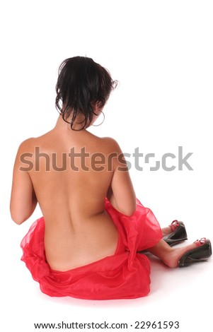 A woman in silk wearing red high-heeled shoes sitting with her back to the camera over white background - stock photo