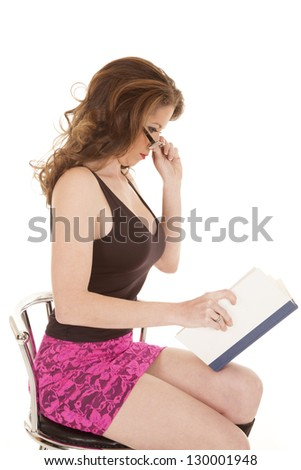 A woman in sitting in a pink skirt reading a book
