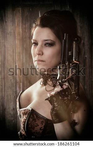 a woman in steam punk outfit holding a gun and looking into the camera in front of a wooden background - stock photo