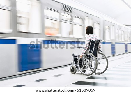 A woman in the wheelchair at the underground station - stock photo