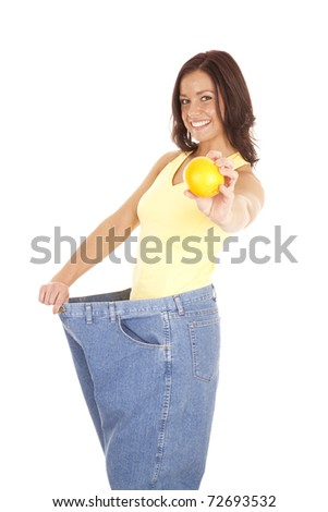 A woman in very large pants is holding out an orange. - stock photo