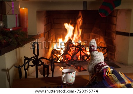 A woman in warm socks in front of a fireplace. Relax