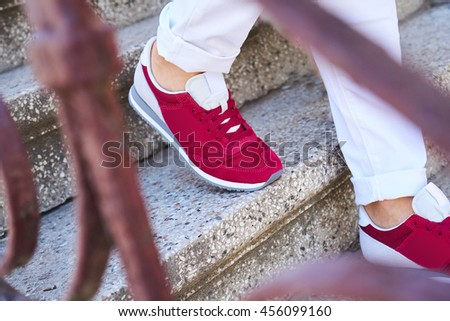 A woman in white pants and red sport shoes on the stairs, fashion style, street style trends - stock photo